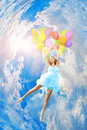Woman holding balloons against sun and sky Stock Images