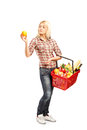 Woman holding a basket full of groceries length portrait young isolated on white background Royalty Free Stock Photo