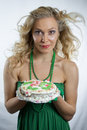 Woman holding birthday cake in green dress Stock Image