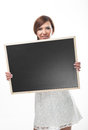 Woman holding a blank chalkboard attractive young rectangular with wooden frame in her hands with copyspace for your text or Royalty Free Stock Images