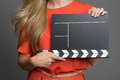 Woman holding a blank clapper board slate on film set with copyspace for your details of time and the number of the take Royalty Free Stock Images