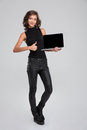 Woman holding blank laptop computer screen and showing thumbs up beautiful attractive curly Stock Photos