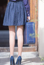 Woman holding blue suitcase back view of s legs in heels elegant Stock Photos