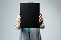 Woman holding a book and showing blank black cover Royalty Free Stock Photo
