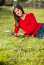 Woman holding books while relaxing on grass at portrait of beautiful young college campus Stock Photo