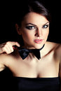Woman holding bow tie portrait of young beautiful girl wearing smoking against black background Stock Image
