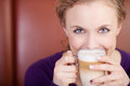 Woman holding cafe latte cup in coffee shop portrait of young Stock Photography