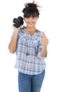 Woman holding camera and giving thumb up on white background Stock Photography