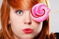 Woman holding candy. Redhair girl with sweet lollipop making fun Royalty Free Stock Photo