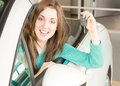 Woman holding car key inside car dealership smiling young Stock Images