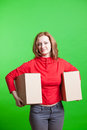 Woman holding cardboard boxes on green background Royalty Free Stock Photo