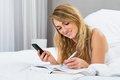 Woman holding cellphone writing in diary Royalty Free Stock Photo