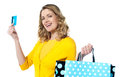 Woman holding cerdit-card with shopping bags Stock Image
