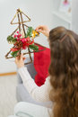 Woman holding Christmas decoration tree. Rear view Stock Photo
