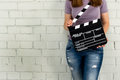 Woman holding a clapboard against brick wall with copy space Royalty Free Stock Photos