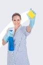 Woman holding cleaning liquid and scrubber over white background Royalty Free Stock Photos