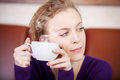 Woman holding coffee cup while looking away in cafe closeup of young Royalty Free Stock Image
