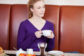Woman holding coffee cup while looking away young in cafe Royalty Free Stock Photo