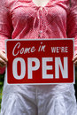 Woman holding come in we're open sign Stock Photography