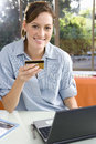 Woman holding credit card by laptop, smiling, portrait Royalty Free Stock Photo