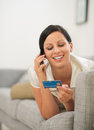 Woman holding credit card and speaking moble Stock Photo