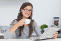 Woman holding a cup of coffee while reading a newspaper pretty Royalty Free Stock Image