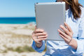 Woman holding digital tablet at beach midsection of Royalty Free Stock Images