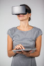 Woman holding digital tablet and using virtual reality headset