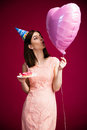 Woman holding donut with candle and heart shaped balloon Royalty Free Stock Photo