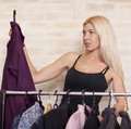 Woman holding dress on coathanger by clothing rail Stock Photography