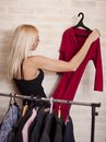 Woman holding dress on coathanger by clothing rail Royalty Free Stock Image