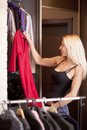 Woman holding dress on coathanger by clothing rail Stock Images