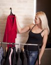 Woman holding dress on coathanger by clothing rail Stock Photo