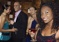 Woman holding drink with people at bar portrait of a young women in the Royalty Free Stock Image