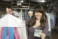 Woman holding dry cleaned clothes and receipt portrait of happy young women in laundry Royalty Free Stock Photography