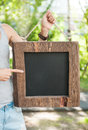 Woman holding empty blackboard with wooden frame. Template Mock Royalty Free Stock Photo