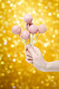 Woman holding a few pink cake pops in hand party dessert Stock Photos