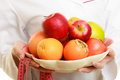 Woman holding fruits dietitian recommending healthy food closeup in white lab coat and colorful measure tapes doctor dieting Royalty Free Stock Photo