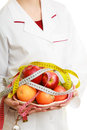 Woman holding fruits dietitian recommending healthy food closeup in white lab coat and colorful measure tapes isolated doctor Stock Images