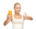 Woman holding glass of orange juice and showing thumbs up Stock Images