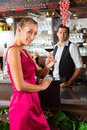 Woman holding a glass of wine in hand at the bar Royalty Free Stock Image