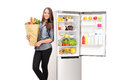 Woman holding a grocery bag by an open fridge isolated on white background Stock Photos