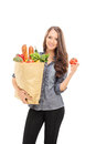 Woman holding grocery bag and a single tomato isolated on white background Royalty Free Stock Photo