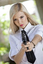 Woman holding gun in blouse and tie angry white shirt aiming the the camera Stock Photo