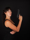 Woman holding a gun holdin against dark background Stock Photography