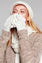 Woman holding a handkerchief and sneezing isolated on grey Royalty Free Stock Photography
