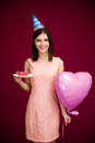Woman holding heart shaped balloon and donut with candle Royalty Free Stock Photo