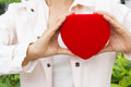 Woman holding heart shaped red box next to her chest Royalty Free Stock Image