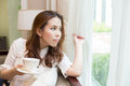 Woman holding her coffee cup a is and looking out of the window Royalty Free Stock Images