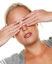 Woman holding her eyes to a young on the photo icon for not wanting see and displacement as well as dispute avoidance Stock Photos